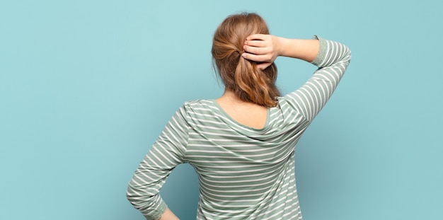 Блондинка красивая женщина думает или сомневается, почесывает голову, чувствует озадаченность и замешательство, вид сзади или сзади