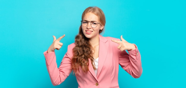 Блондинка красивая женщина с плохим отношением выглядит гордо и агрессивно, указывая вверх или весело жестикулируя руками