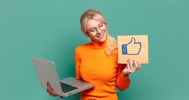 ラップトップを持つ金髪のきれいな女性。コンセプトのようなソーシャルメディア