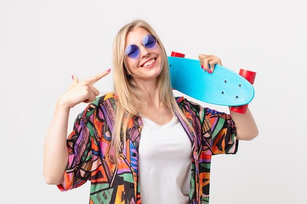 スケートボードを持つ金髪のきれいな女性。夏のコンセプト