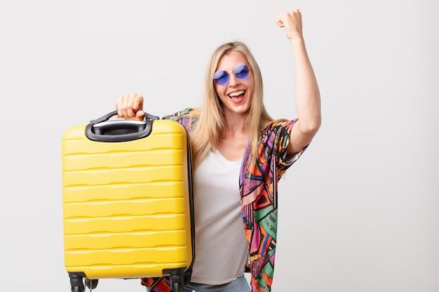 スーツケースを持つ金髪のきれいな女性。夏のコンセプト
