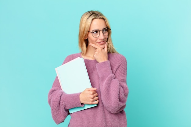 Blonde pretty woman with books studing
