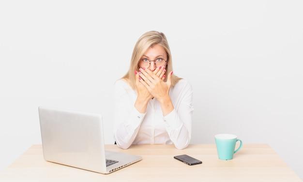 金髪のきれいな女性若いブロンドの女性はショックを受けてラップトップで作業している手で口を覆っている