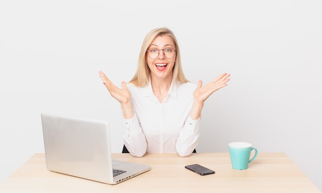 金髪のきれいな女性若いブロンドの女性は、信じられないほどの何かに幸せと驚きを感じ、ラップトップで作業しています