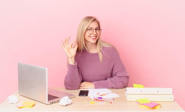 金髪のきれいな女性若い金髪の女性は幸せを感じ、大丈夫なジェスチャーで承認を示し、ラップトップで作業します