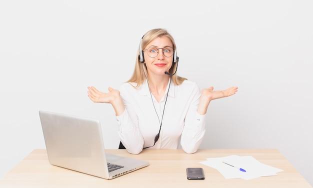 금발의 예쁜 여자 젊은 금발의 여자는 어리둥절하고 혼란스럽고 의심하고 노트북으로 작업합니다.