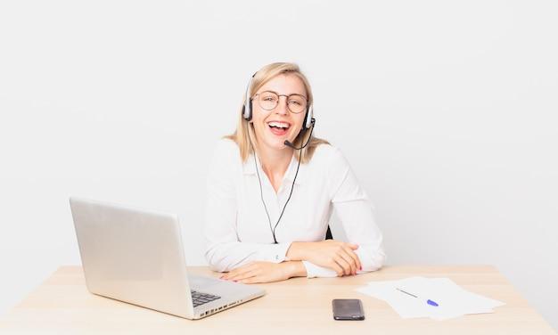 いくつかの陽気な冗談で大声で笑って、ラップトップで作業している金髪のきれいな女性若い金髪の女性