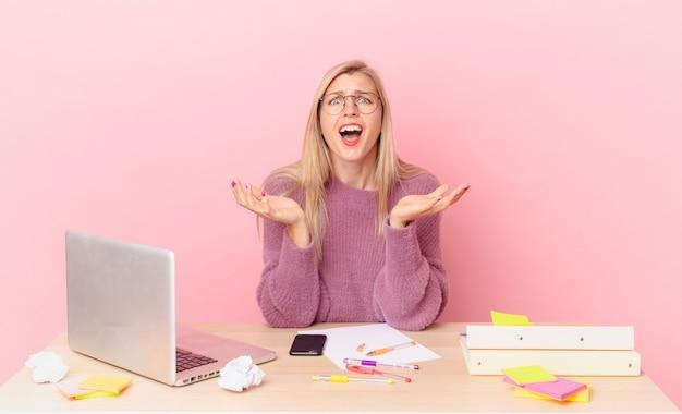 금발의 예쁜 여자 젊은 금발의 여자는 절망적이고, 좌절하고, 스트레스를 받고 노트북으로 일하고 있습니다.