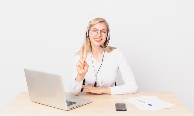 金髪のきれいな女性若い金髪の女性は笑顔でフレンドリーに見え、2番目を示し、ラップトップで作業しています