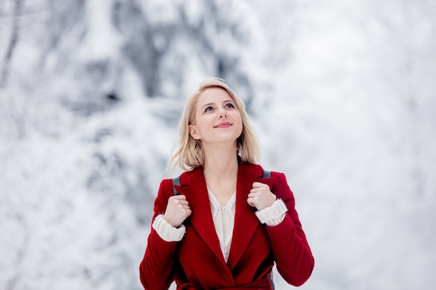Blonde in a red coat in a snowy forest