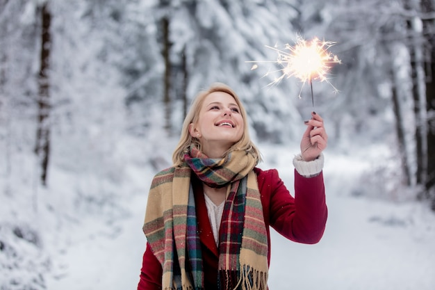Blonde in a red coat with sparkler in a snowy forest