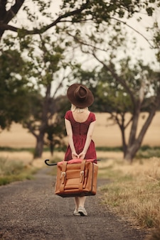 Blonde in red dress with a suitcase on a rural road before the rain