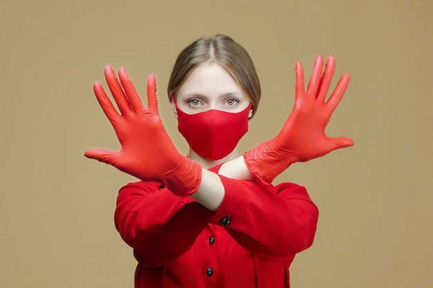 Blonde in red gloves and a mask shows the sign stop with her hands. the concept of preventing coronavirus covid 19.