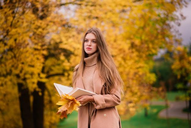 秋の公園を歩いている金髪の赤毛の若い女性。