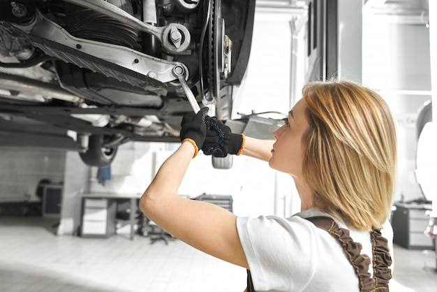 Blonde repairing auto undercarriage with wrench.