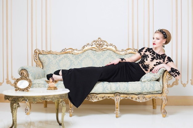 Blonde royal woman on a retro sofa in gorgeous luxury dress with glass of wine in her hand. indoor. copy space