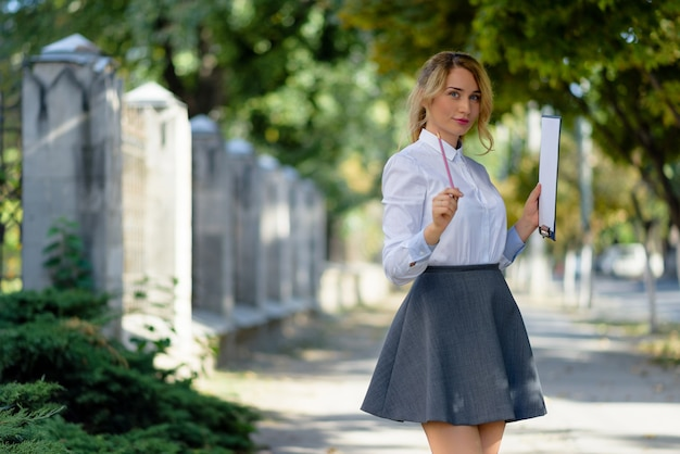 Blonde school girl posing with pencil and paper Premium Photo