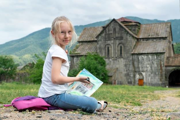 Блондинка школьница рисует в древнем монастыре с лицом, испачканным краской