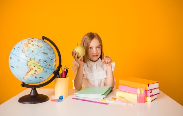 A blonde schoolgirl is sitting at a table with school supplies on a yellow background