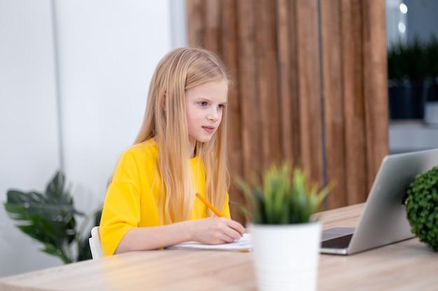 온라인으로 노트북 원격 학습으로 학교 숙제를 하고 집에서 공부하는 금발 여학생