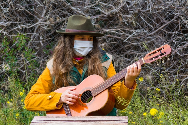 Blonde scout girl with face mask playing guitar. she wears a green vest and a green hat. prepared to face the virus.