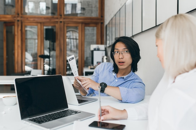 Segretaria bionda seduta con il telefono accanto al computer portatile con schermo nero e ascolto giovane asiatico in bicchieri. impiegato di ufficio cinese castana che parla con il responsabile femminile in camicetta bianca.