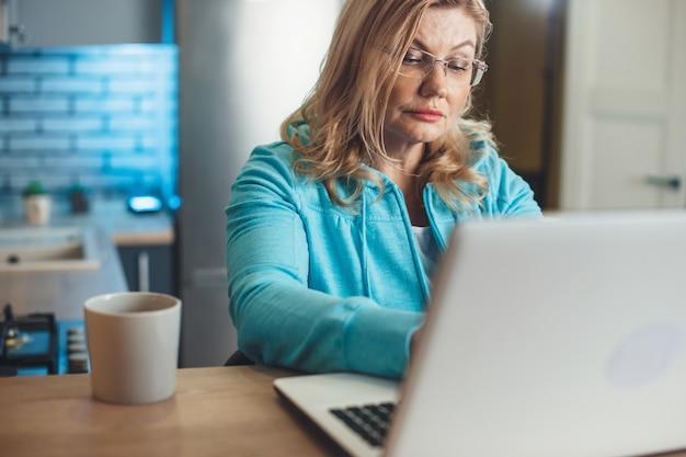 Блондинка старшая женщина работает за ноутбуком из дома, пьет чашку чая на кухне