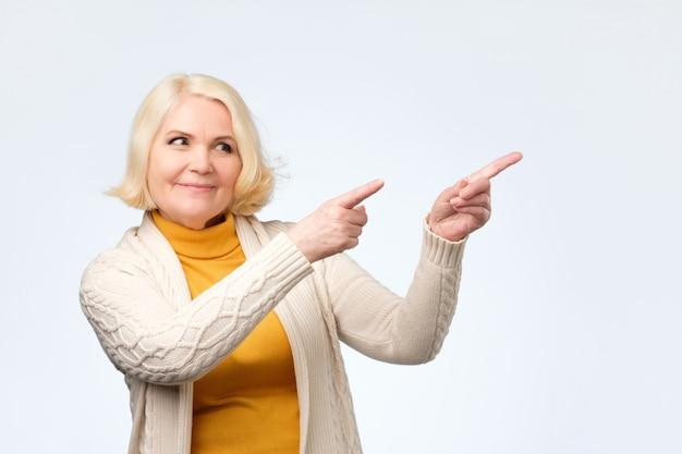 金髪の年配の女性の人差し指を脇に笑って