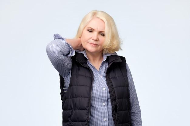 首の痛みで疲れている金髪の年配の女性