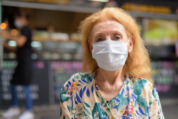 야외 커피 숍에서 코로나 바이러스 발생으로부터 보호하기 위해 마스크와 금발 고위 여자