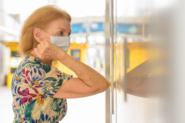 Blonde senior woman with mask pressing elevator button with elbow to avoid spreading the coronavirus covid-19