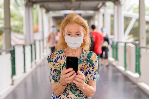 Блондинка старший женщина с маской, используя телефон на пешеходном мосту