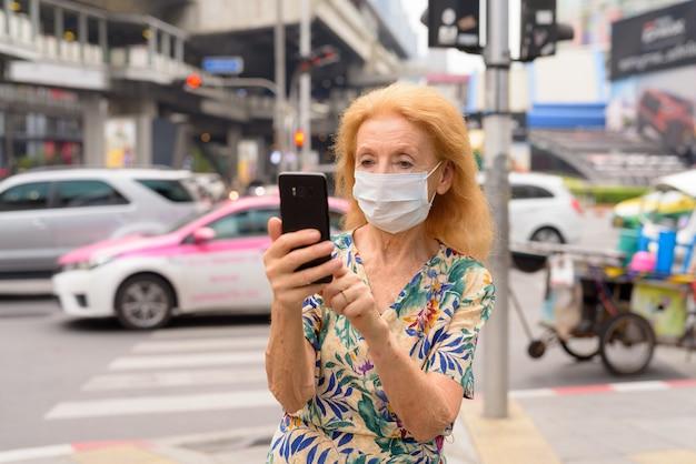 Блондинка старшая женщина с маской с помощью телефона в городе на открытом воздухе