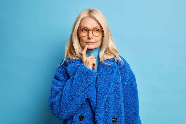 Blonde serious middle aged woman being deep in thoughts keeps index finger on chin tries to make right decision in mind wears blue fur coat.