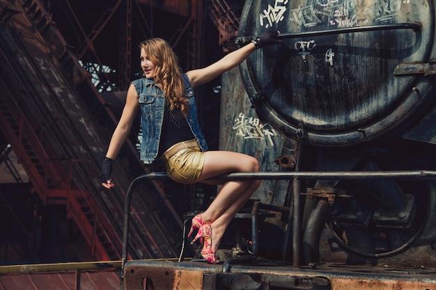 ショートパンツとかかとの古い工場で金髪のセクシーな女の子