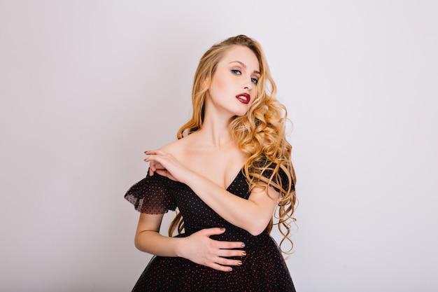 ブロンドのセクシーな女の子、ポーズ、官能的に見て、いちゃつく長い美しい巻き毛のモデル。黒いドレスを着て、肩を開けて明るいメイクをしています。白で隔離されます。