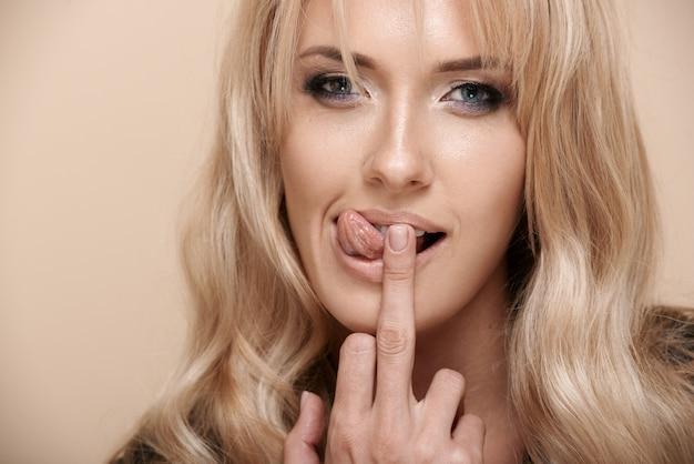 舌と中指を示す金髪のセクシーな女性