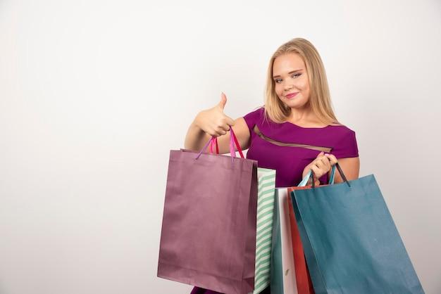 화려한 쇼핑 가방을 잔뜩 들고 금발 쇼핑 중독. 고품질 사진