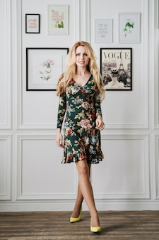 Blonde in short green dress with patterns. beautiful girl in a white studio.