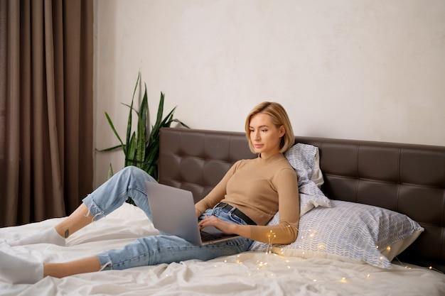 노트북 컴퓨터와 청바지에 흰색 침대에 금발 짧은 머리 여자.