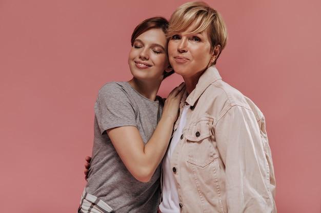Блондинка с короткими волосами в бежевой куртке смотрит в камеру и обнимается с молодой девушкой в серой футболке с закрытыми глазами на розовом фоне.