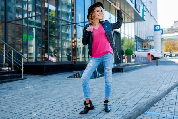 Blonde short haired woman walking on streets of big modern city. fashionable urban outfit. unusual pink sunglasses.