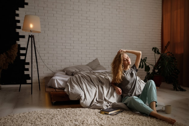 Блондинка сидит возле кровати по утрам