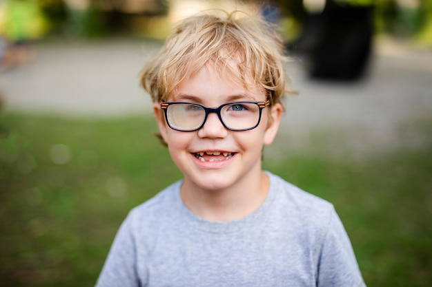 Blonde smiling boy with strabismus wearing glasses with special lens in warm park