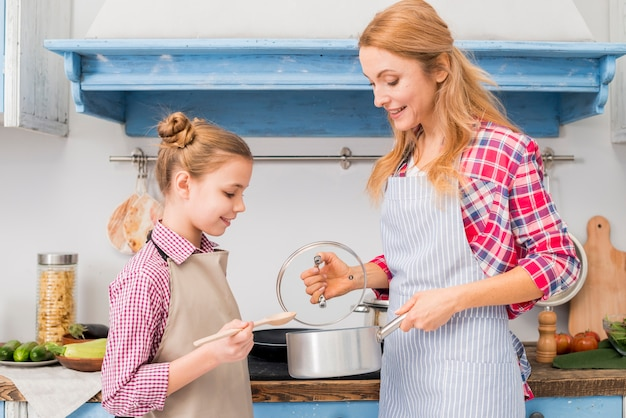Blonde smiling female showing cooking pot to her daughter in the kitchen