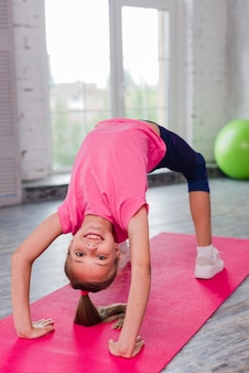 Blonde smiling girl exercising on pink exercise mat
