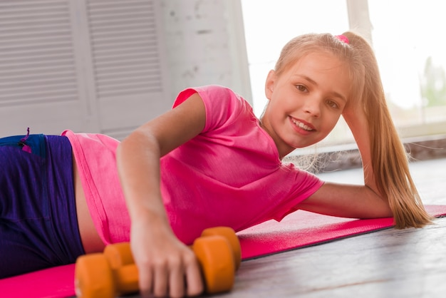 Blonde smiling girl lying on pink exercise mat with an orange dumbbell