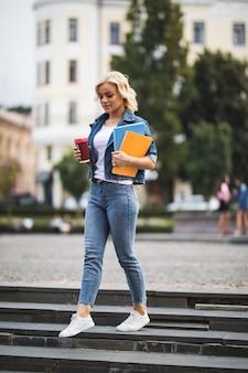 Modello di ragazza sorridente bionda sta andando alle lezioni di lavoro attraverso il citycentre tenendo il computer del caffè notebook tra le mani al mattino