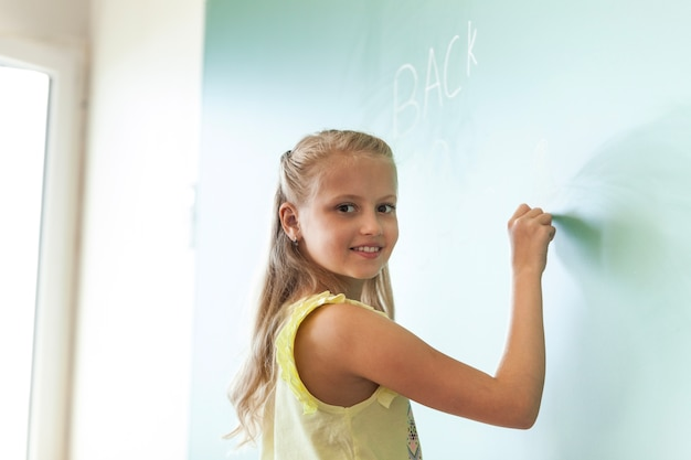 Blonde smiling girl writing on chalkboard