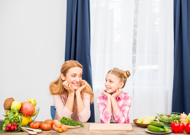 Blonde smiling mother and her daughter looking at each other with vegetables on table